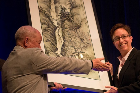 Portland artist Luo Jian presents a painting to Oregon House Speaker Tina Kotek.