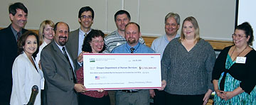 Under Secretary Johner gives symbolic check to Dr. Goldberg and CAF Food Stamp staffers