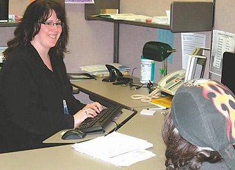Jamie Hoschouer, a food stamp eligibility worker with DHS in Roseburg, talks to a client who came in to get help Monday.